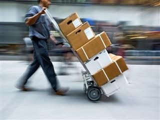 person delivering packages on a hand truck