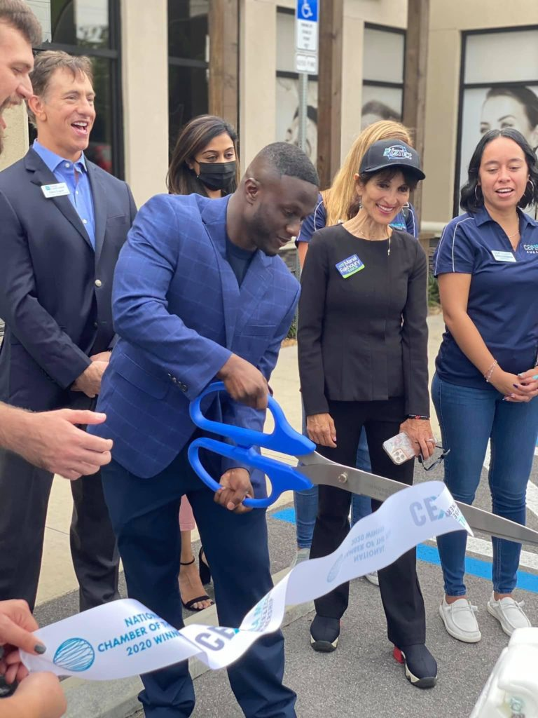 Woodly Oralus cuts the ribbon on the new location for his business Biznct